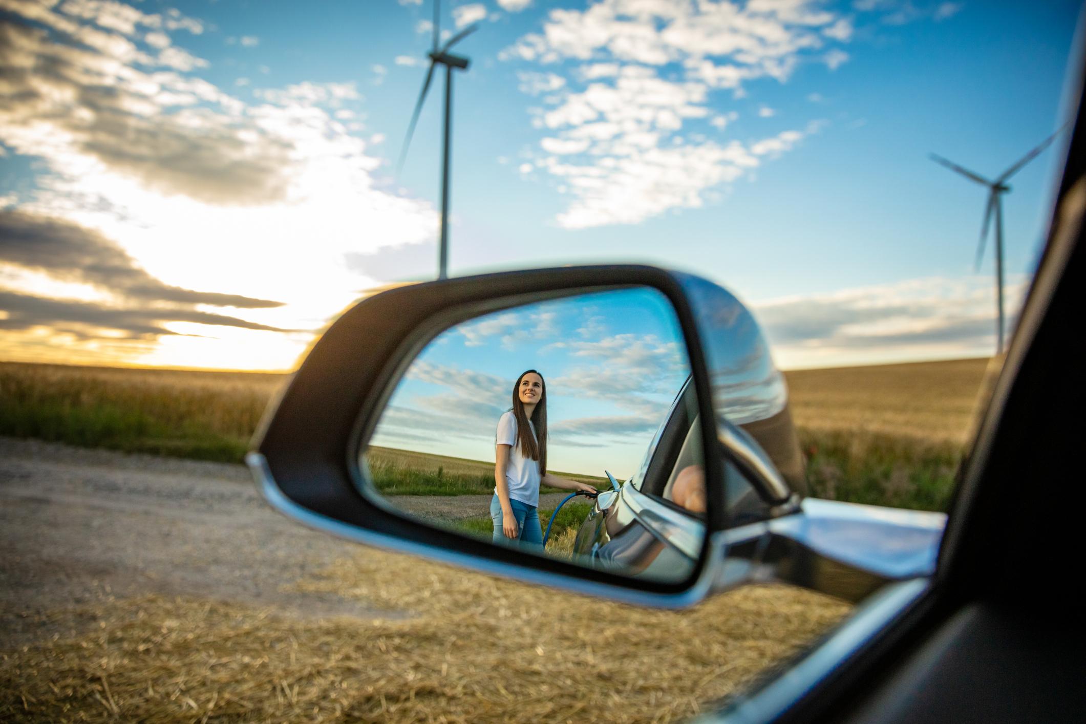 woman charging electric car staring at windmills