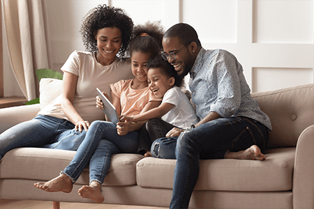 Family Sitting on Couch on Tablet