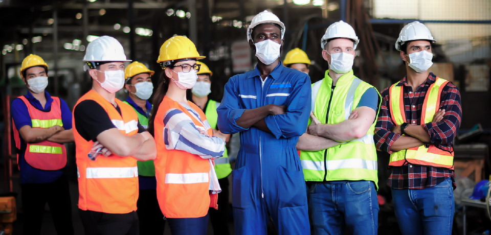 Diverse Workers Standing in Group on Site with Arms Folded