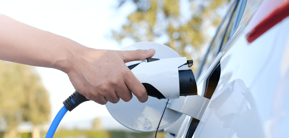 Person Plugging in Their Electric Vehicle (EV) for Charging
