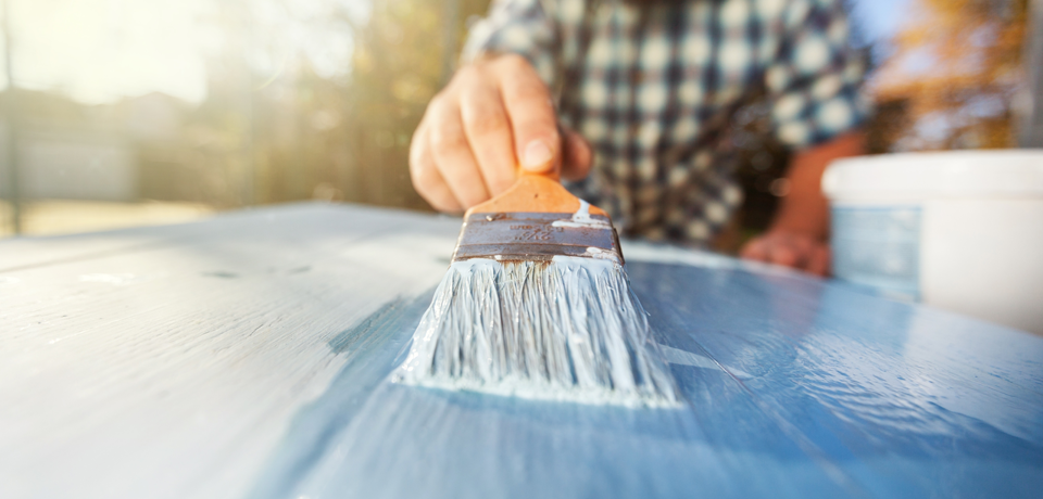 Person Painting Wood with Paint Brush